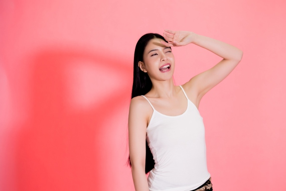 Young beautiful Asian woman scared of sunshine isolated over pink background. Concept for summer skin care and skin protection from uv sunshine
